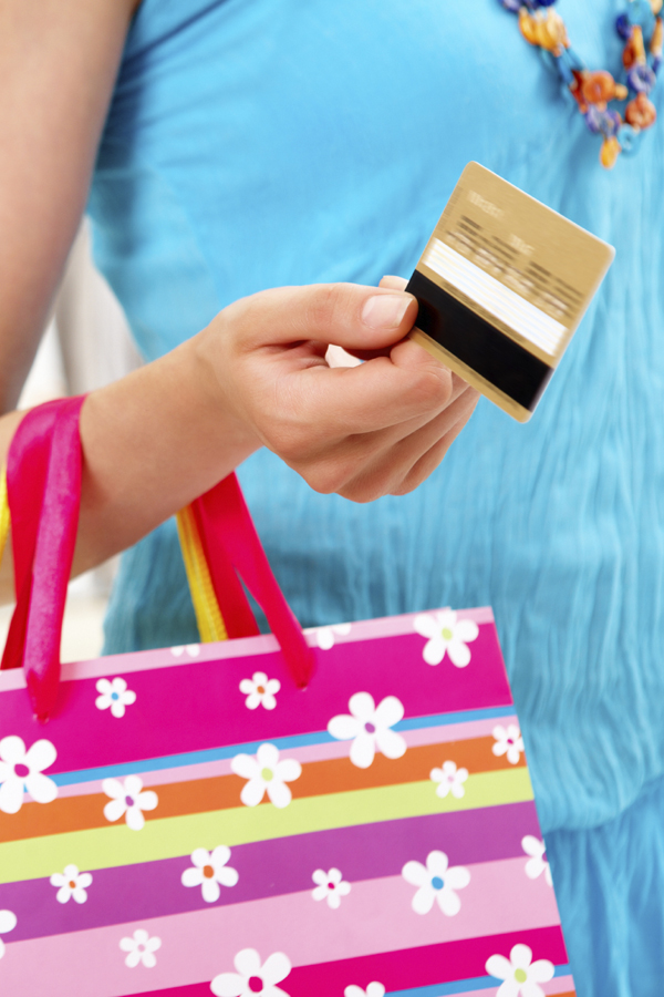 Close-up of woman's hand holding plastic card while going shopping in the mall